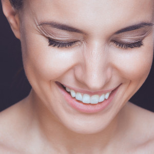 Beautiful young smiling woman with visible wrinkles around her eyes