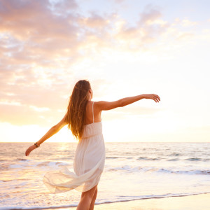 Happy Carefree Woman Dancing on the Beach at Sunset